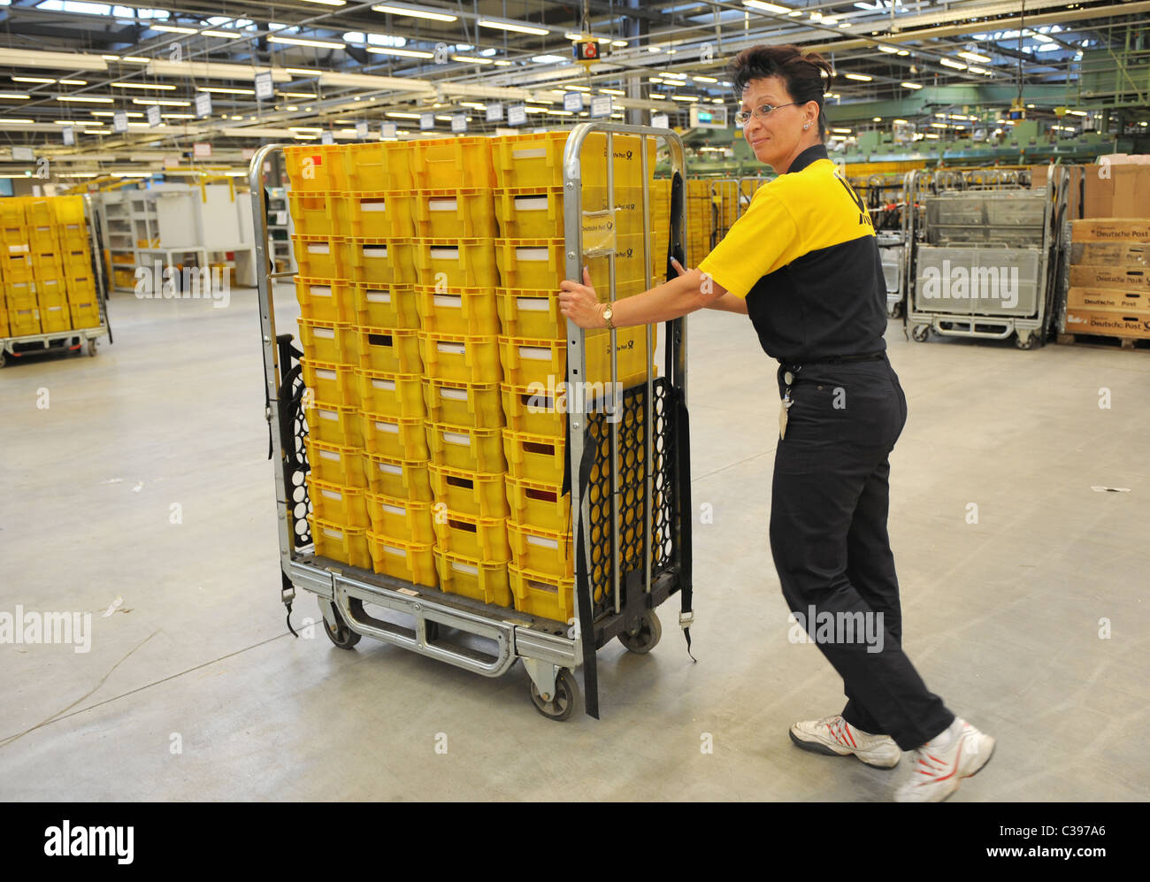 An employee with a trolley in a postal sorting centre, Berlin, Germany - Stock Image