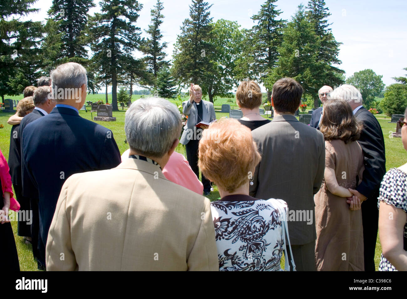 Minister performing graveside committal at a funeral before friends and family at the cemetery. St James Minnesota - Stock Image