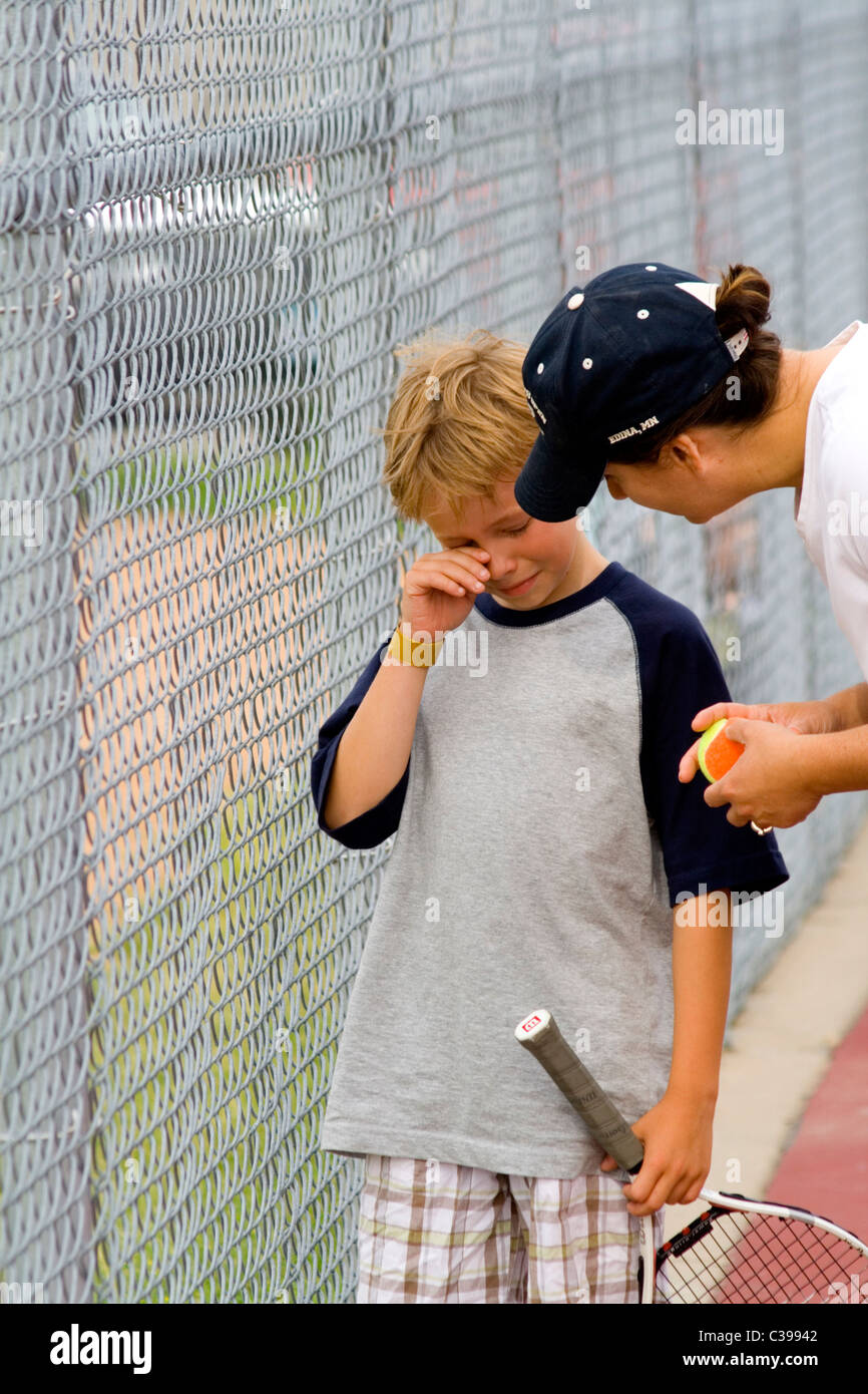 Boy age 8 tearful at the loss at a tennis tournament and received comfort from his mom. St Paul Minnesota MN USA - Stock Image