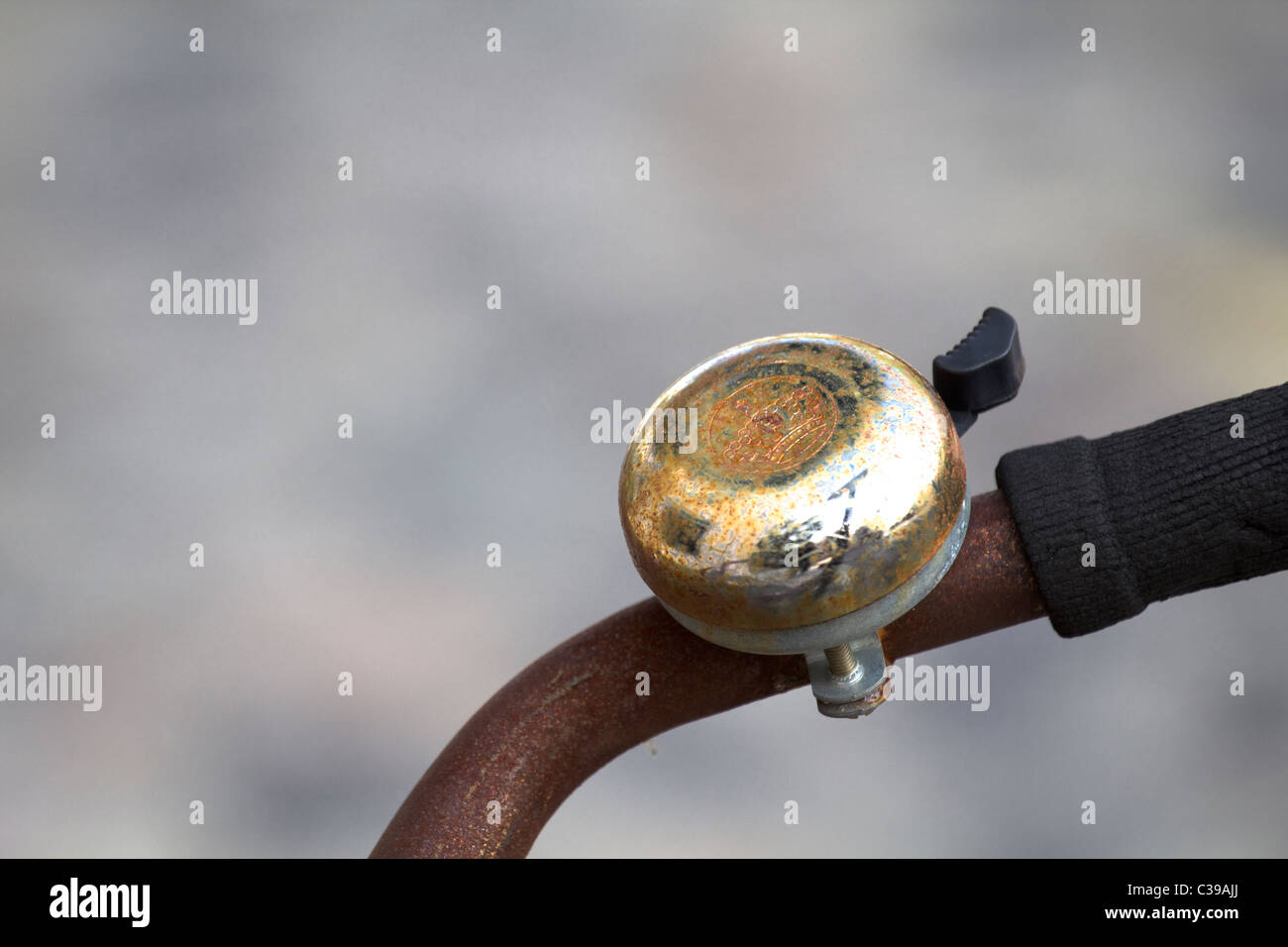 rusty bicycle bell on handle bar - Stock Image