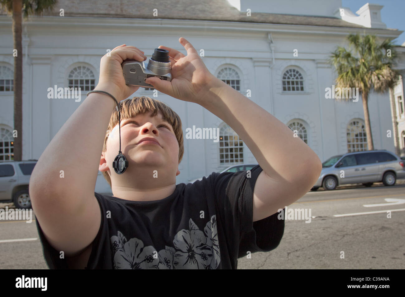young boy using digital camera to take photos - Stock Image