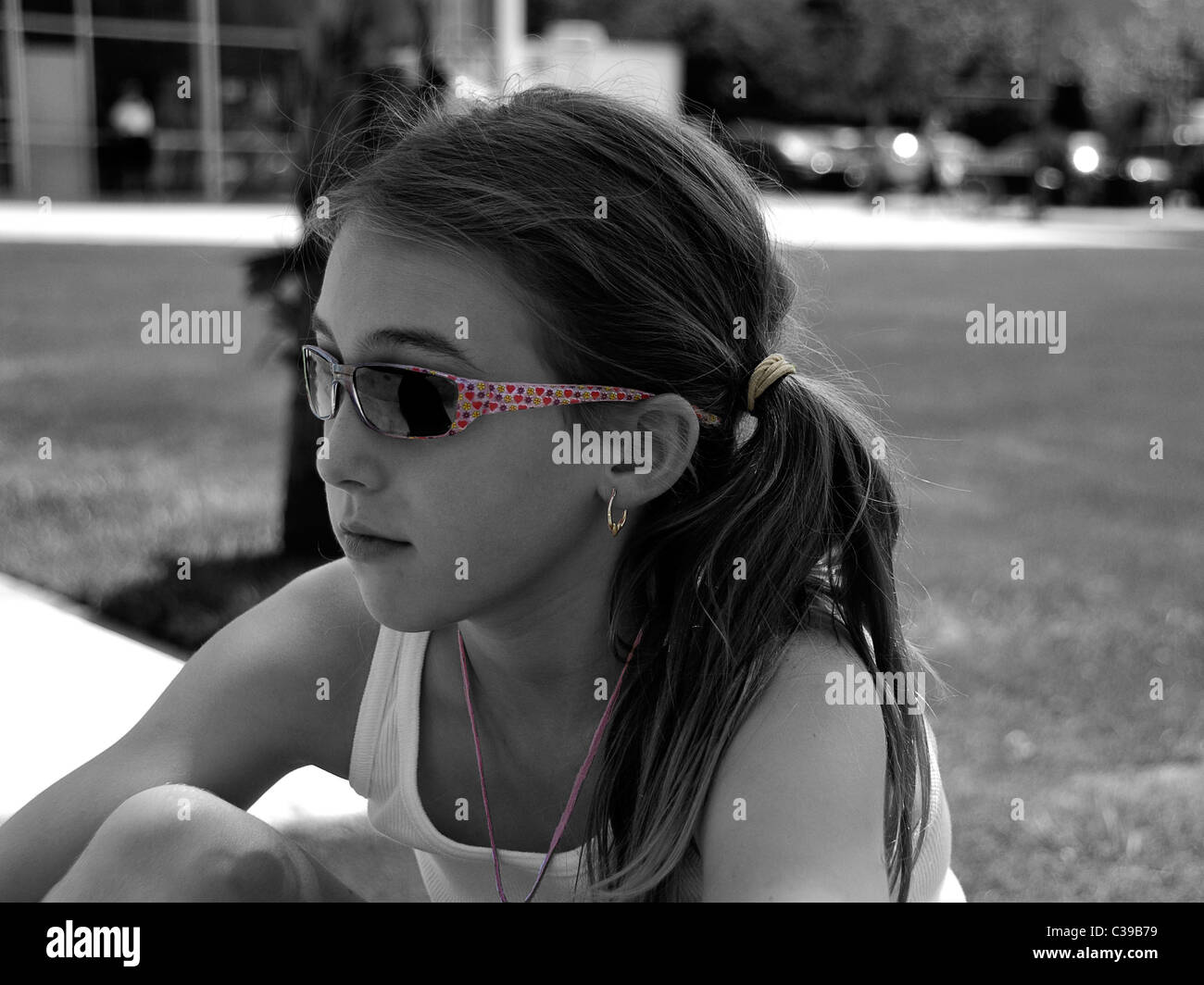 Two-toned photograph of a young girl contemplating life. - Stock Image