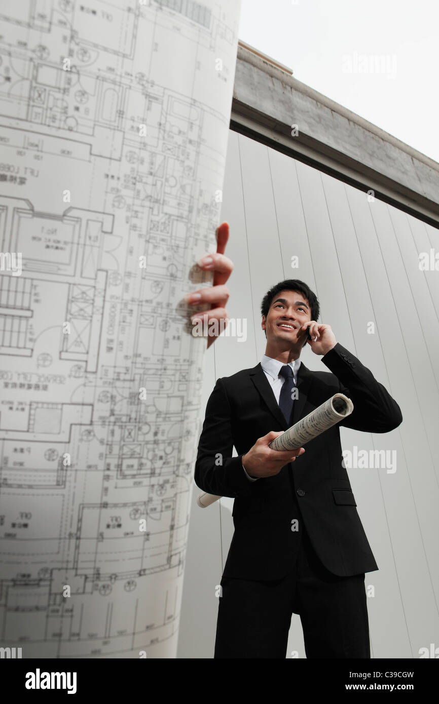 Woman holding building plans while man talks on phone - Stock Image