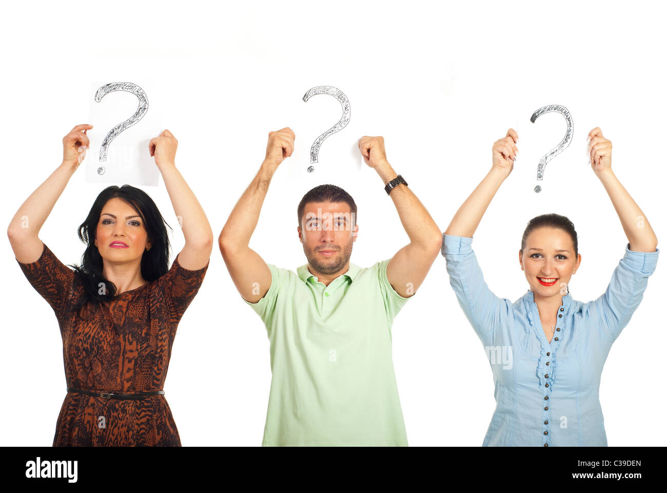 Three casual people standing in a line and holding questions marks over their heads isolated on white background - Stock Image