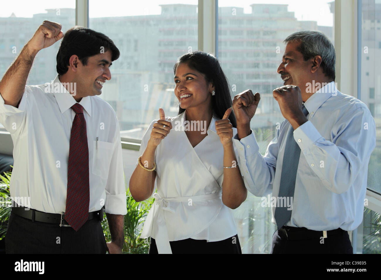 Three Indian people smiling at each other and making hand gestures - Stock Image