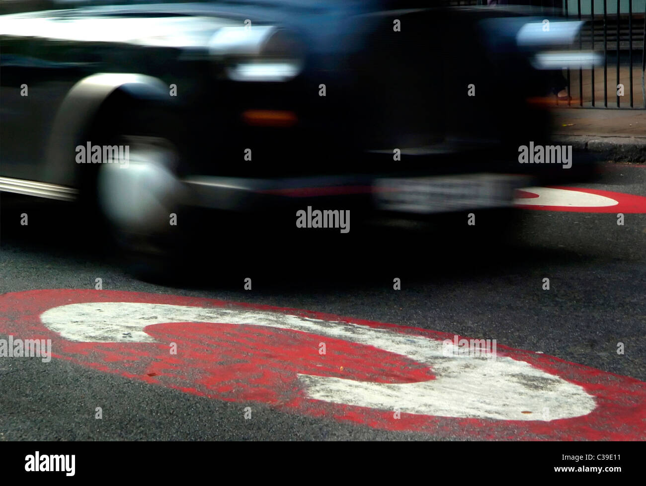 A taxi passes by the sign of the Congestion Charge Zone - Stock Image