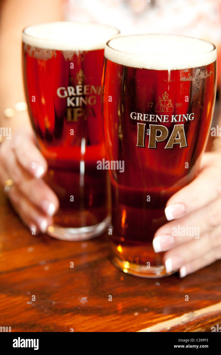 Two pints of Greene King IPA in branded glasses. - Stock Image