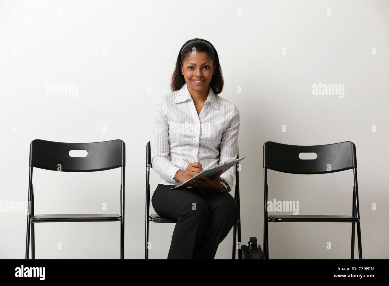 Young Indian woman fills out form and waits in waiting room - Stock Image