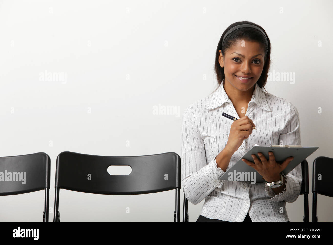 Indian woman fills our form in waiting room - Stock Image