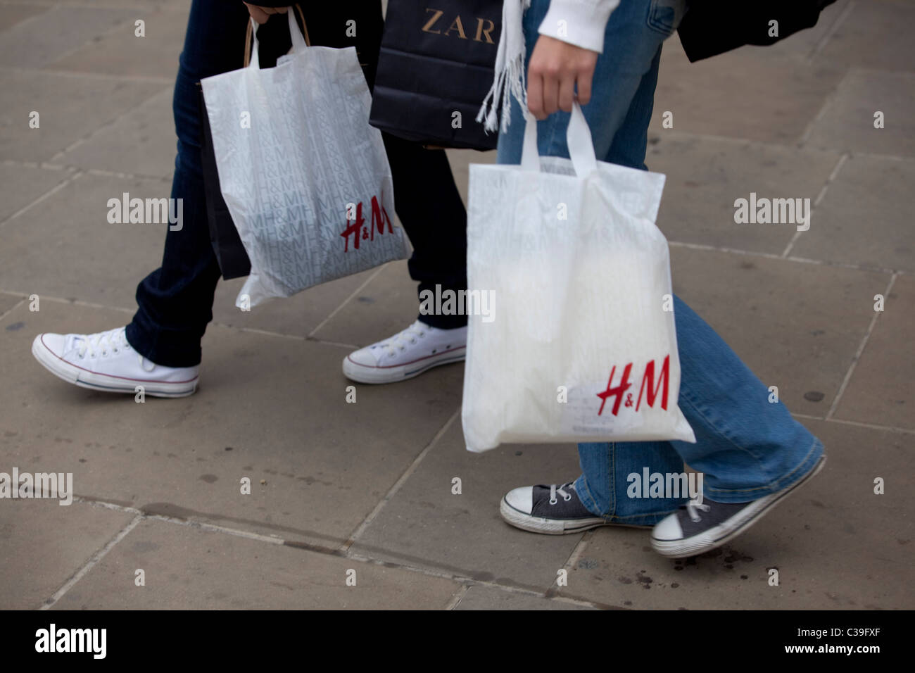 Two H&M customers leaving a store with their purchases. - Stock Image