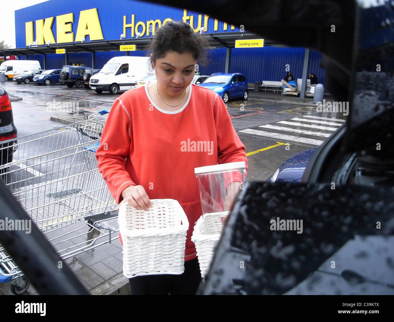 An Ikea customer loading her car with purchases. - Stock Image