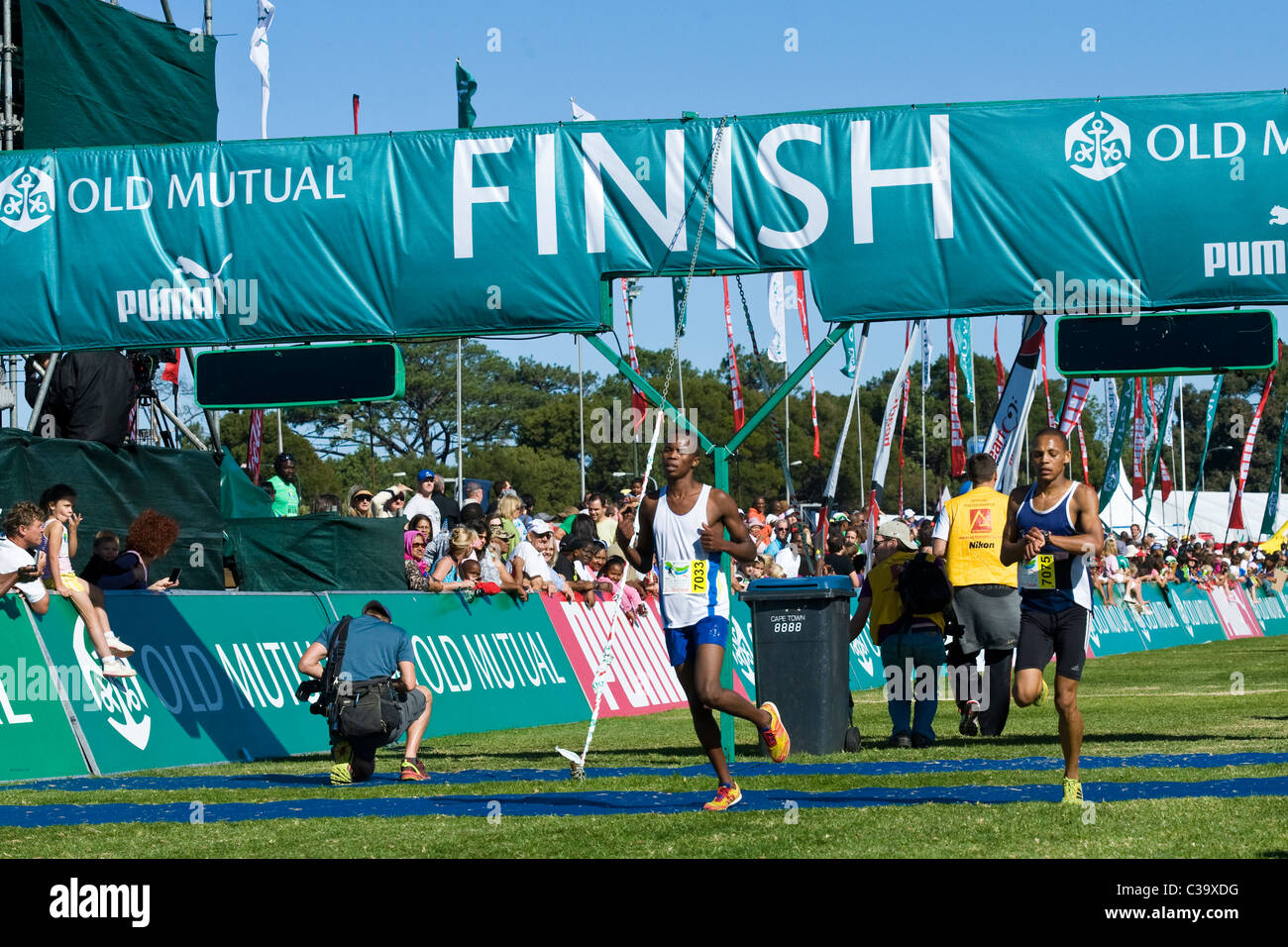 Runners crossing the finish of the 5km Fun Run, Two Oceans Marathon, Cape Town, South Africa - Stock Image