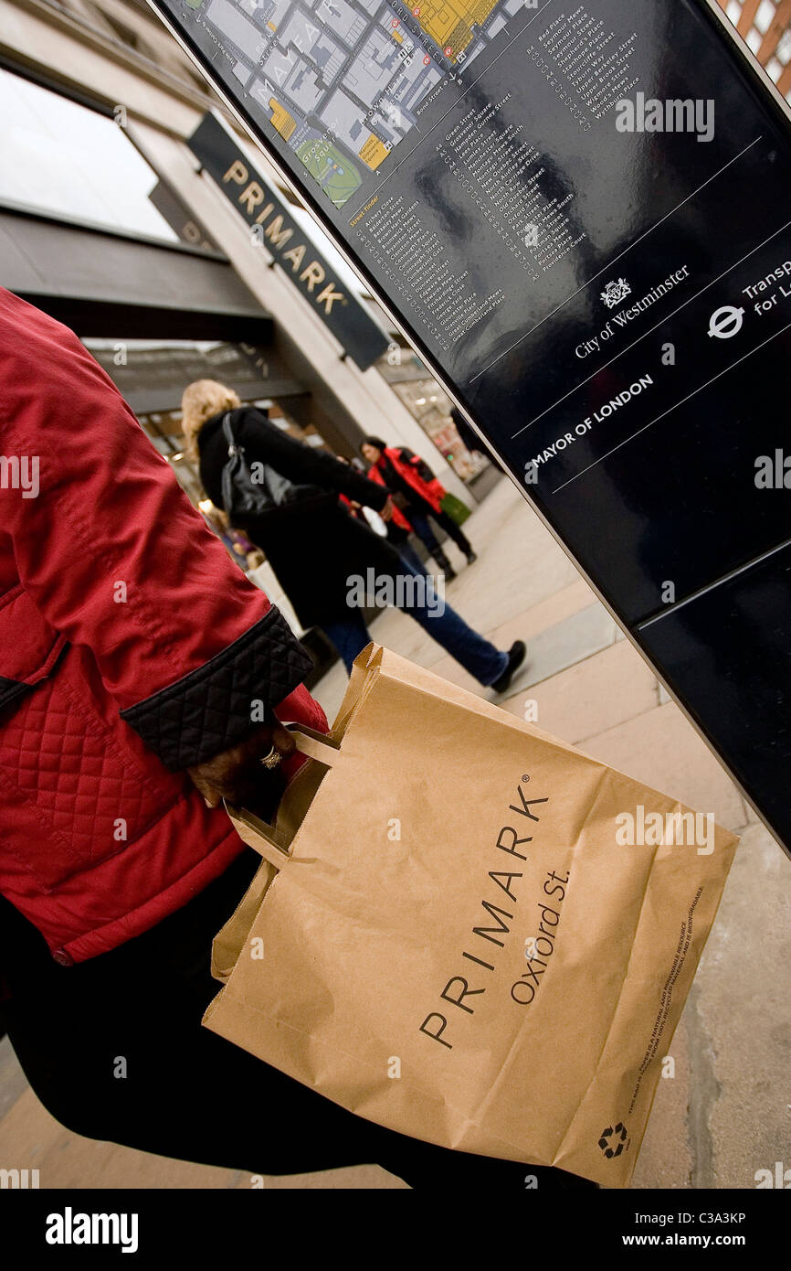 A Primark customer walking down Oxford Street after a day shopping at the flagship store in Central London - Stock Image