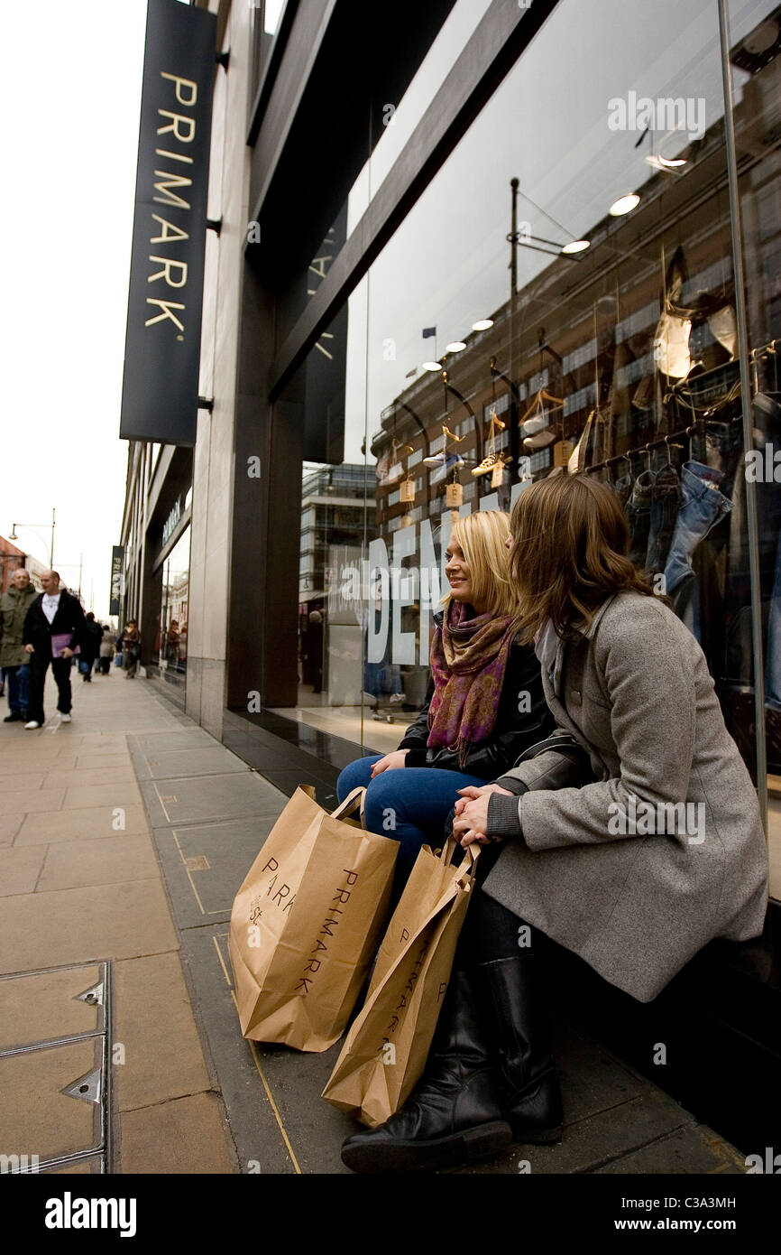 Two Primark customers relax outside the flagship store on Oxford Street, Central London - Stock Image
