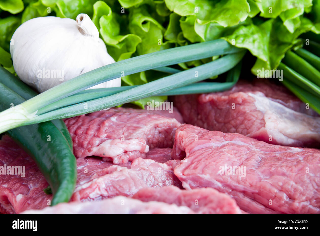 Fresh beef meat with green onion, pepper, garlic and lettuce - Stock Image