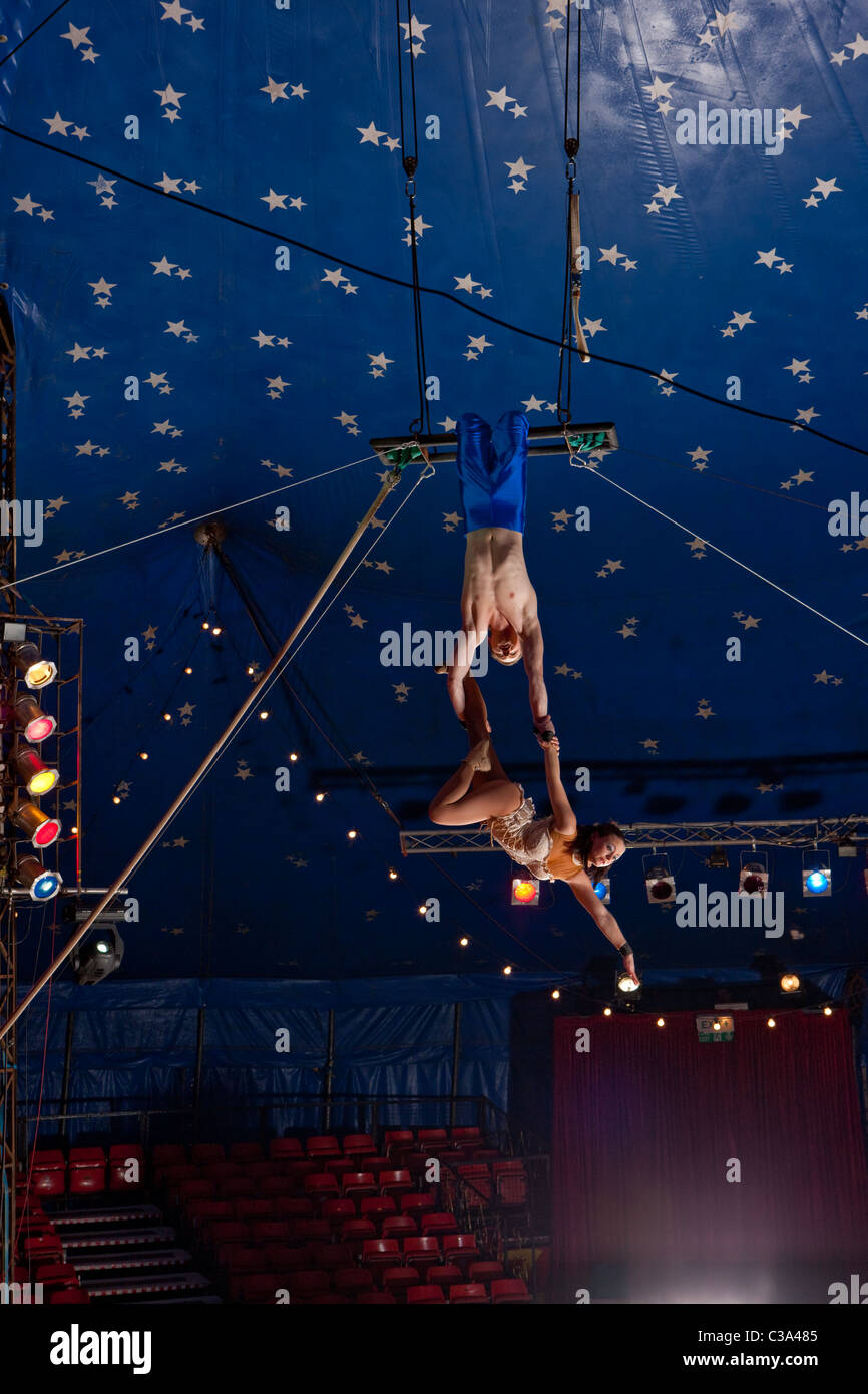 Looking up at circus trapeze artist's - Stock Image