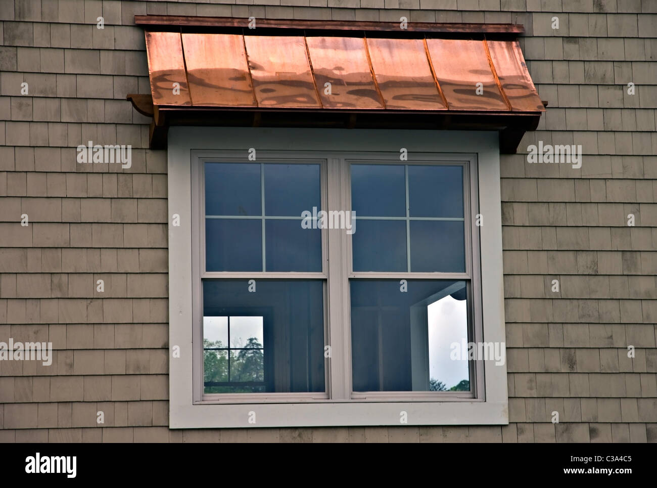 A copper window awning on the side of a building. - Stock Image