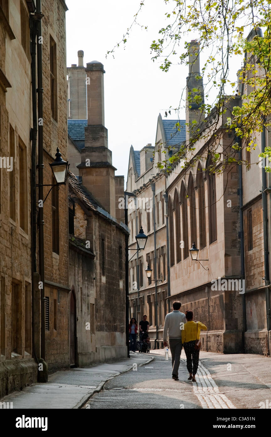 Young couple, arm in arm, walking along a lane amongst the renowned Oxford Colleges - which comprise Oxford university. - Stock Image