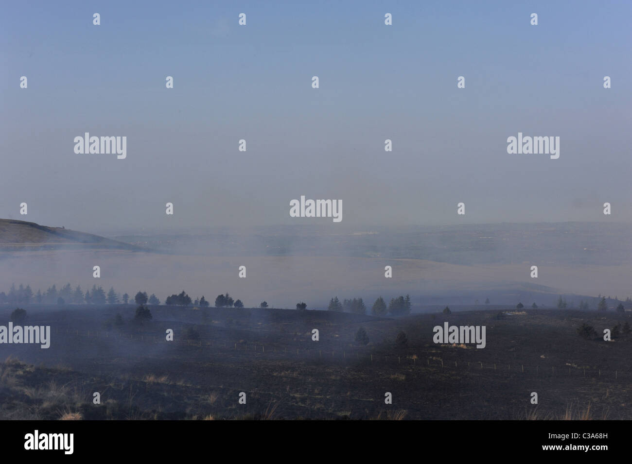 Landscape view of burnt out grass fire with smoke still coming off the remains blowing over the countryside - Stock Image