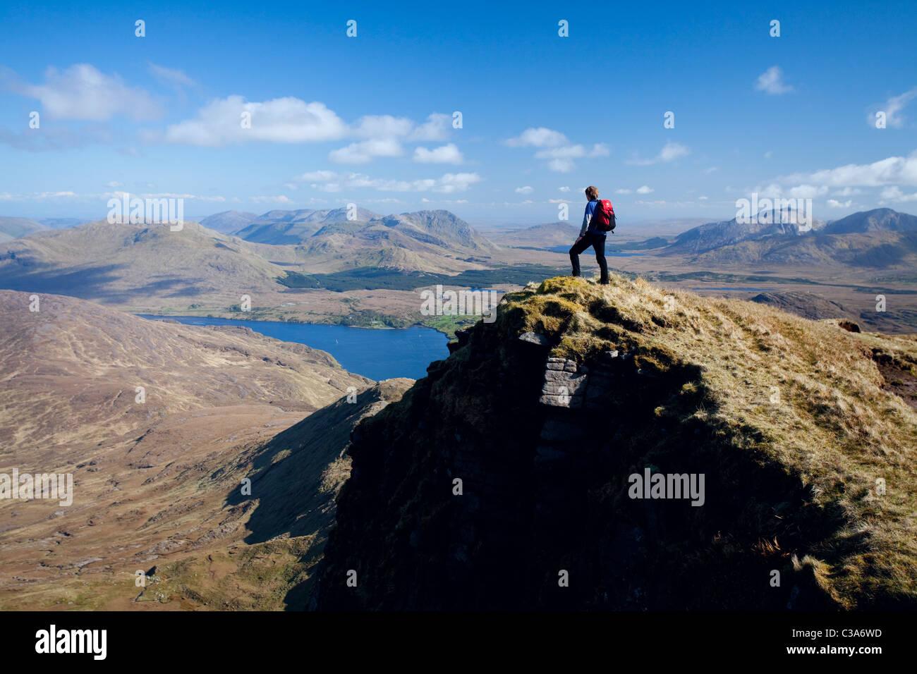 Walker looking across Killary Harbour from the southern ridge of Mweelrea Mountain, County Mayo, Ireland. - Stock Image
