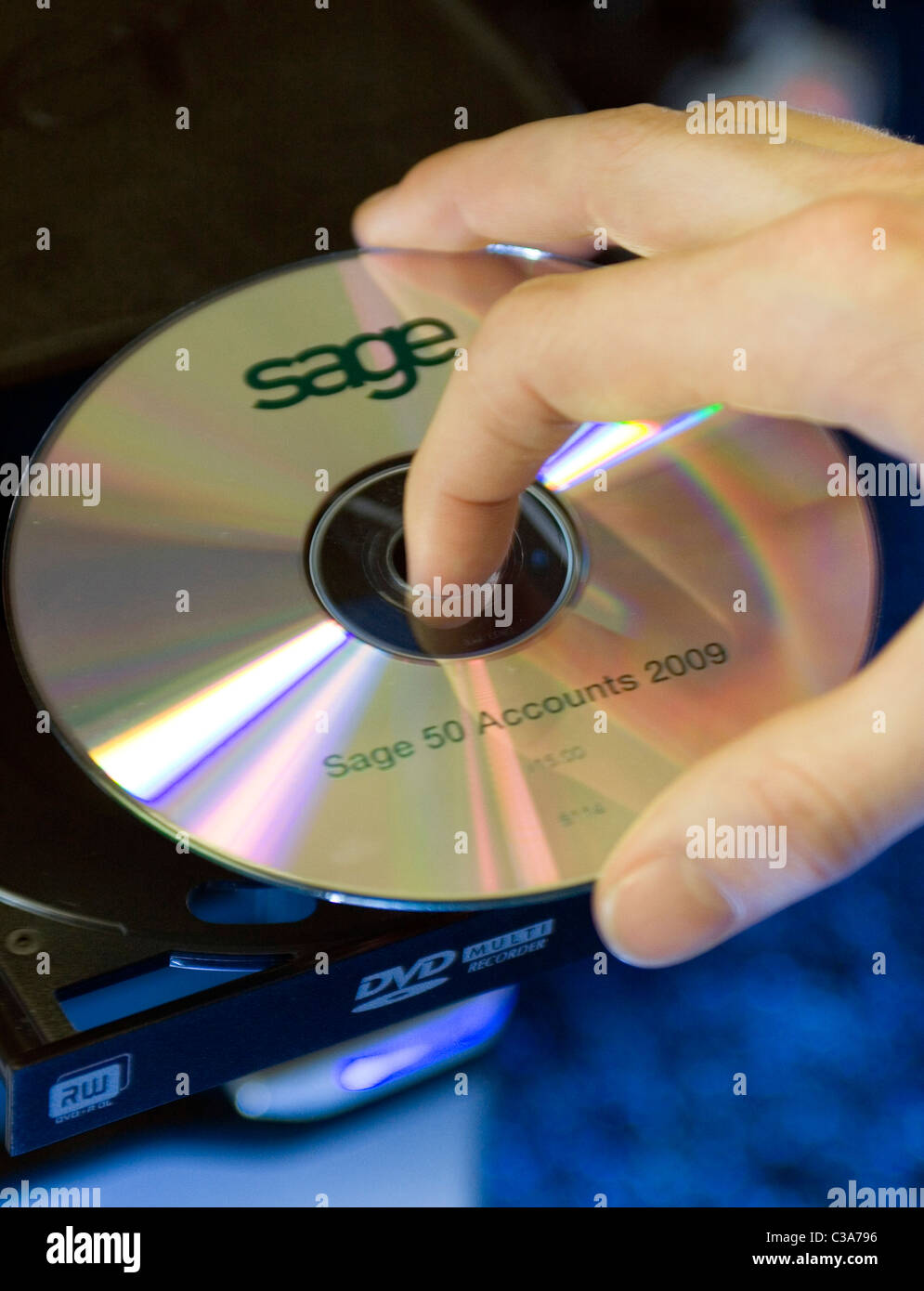 Sage '50 Accounts 2009' installation DVD being placed into PC DVD tray - Stock Image
