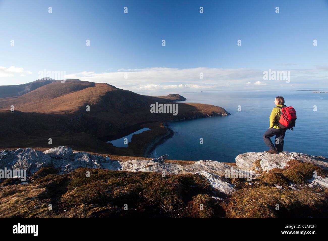 Walker looking across Lough Nakeeroge to Croaghaun, Achill Island, County Mayo, Ireland. - Stock Image