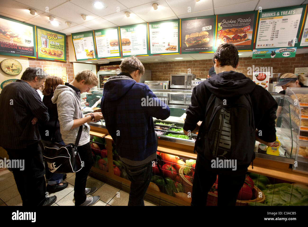 Customers wait in store for their 'subs' to be prepared. - Stock Image