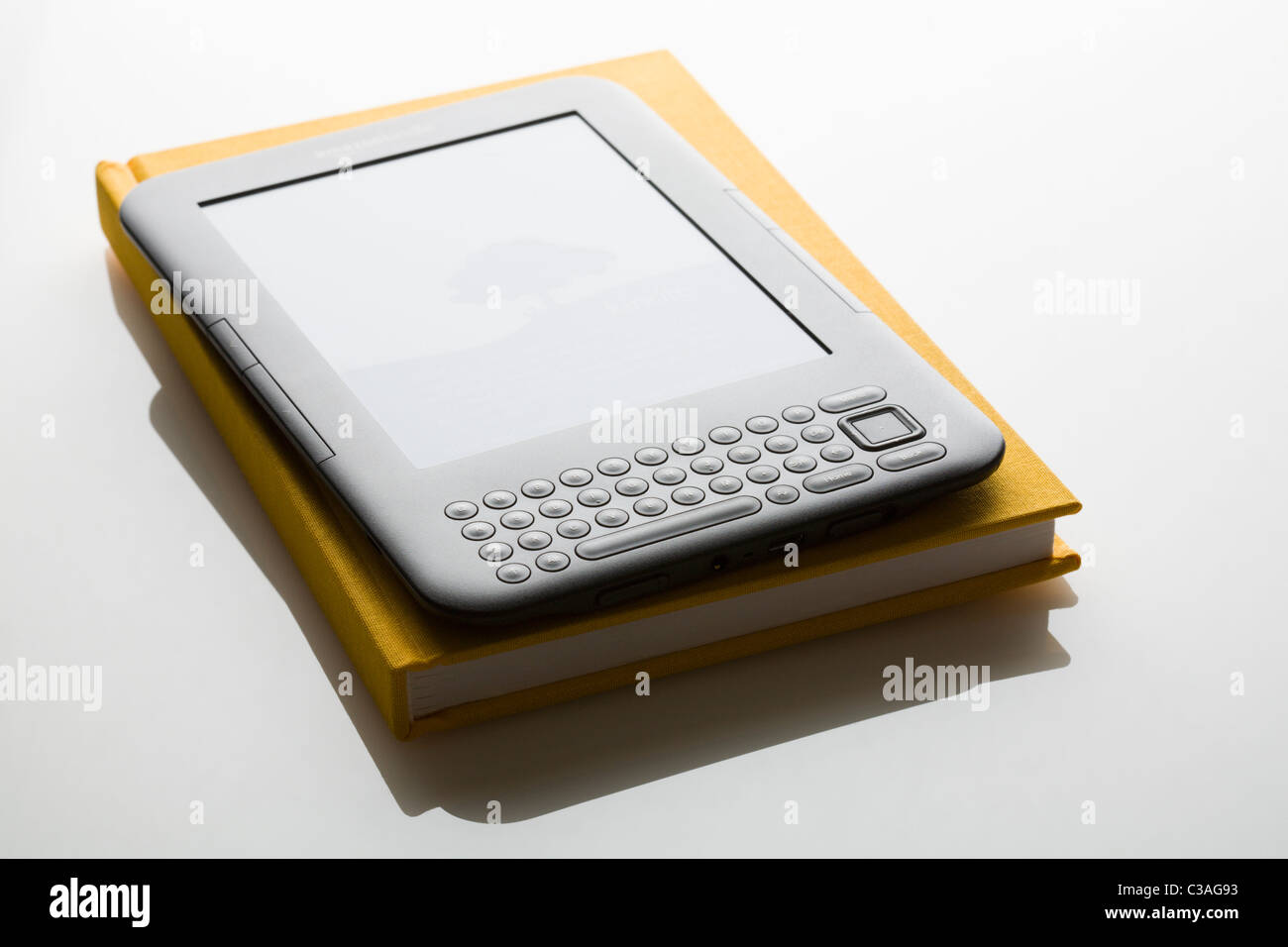Amazon Kindle ebook reader on traditional book FOR EDITORIAL USE ONLY - Stock Image