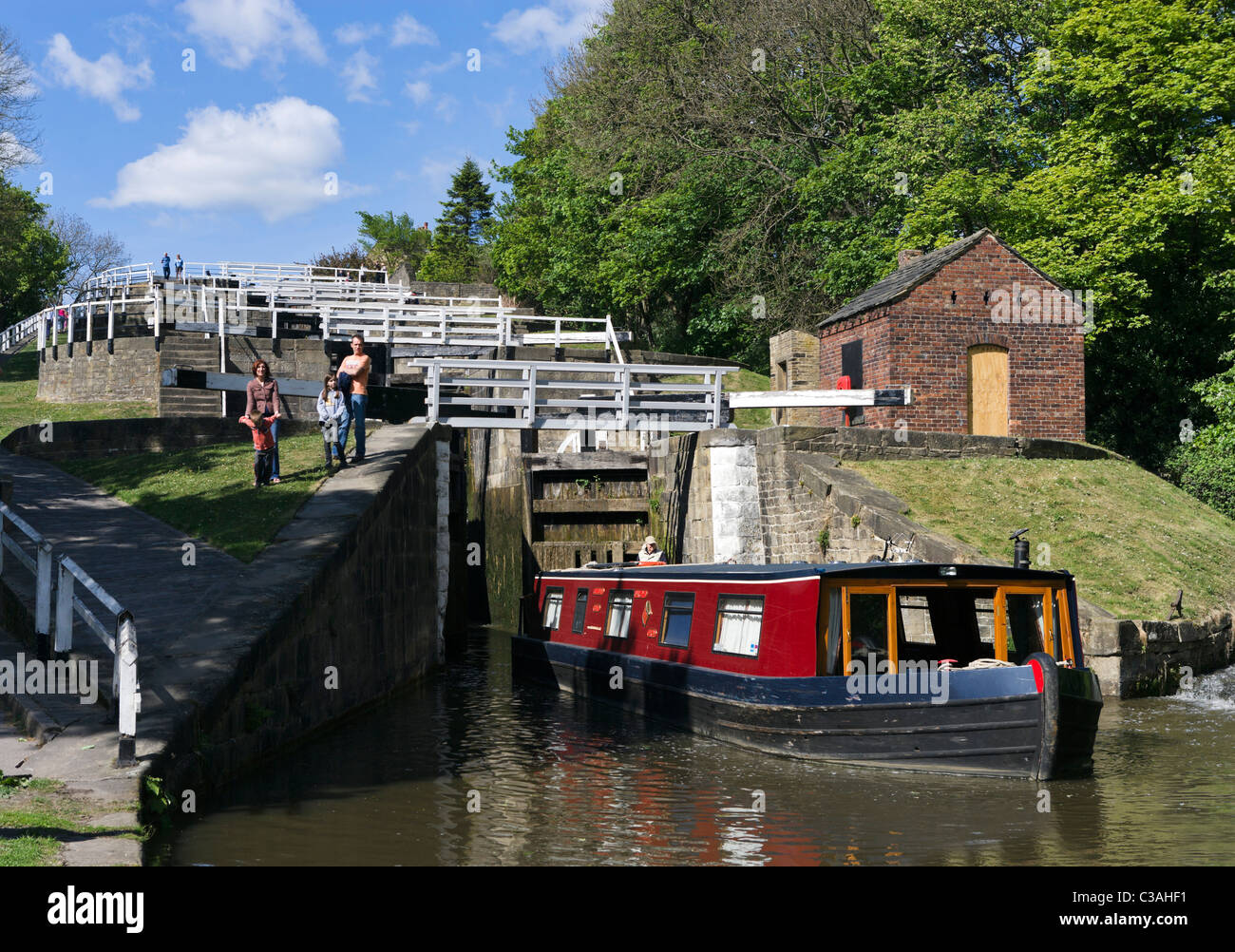Narrowboat leaving the last of the Five Rise Locks on the Leeds and Liverpool Canal, Bingley, West Yorkshire, UK - Stock Image