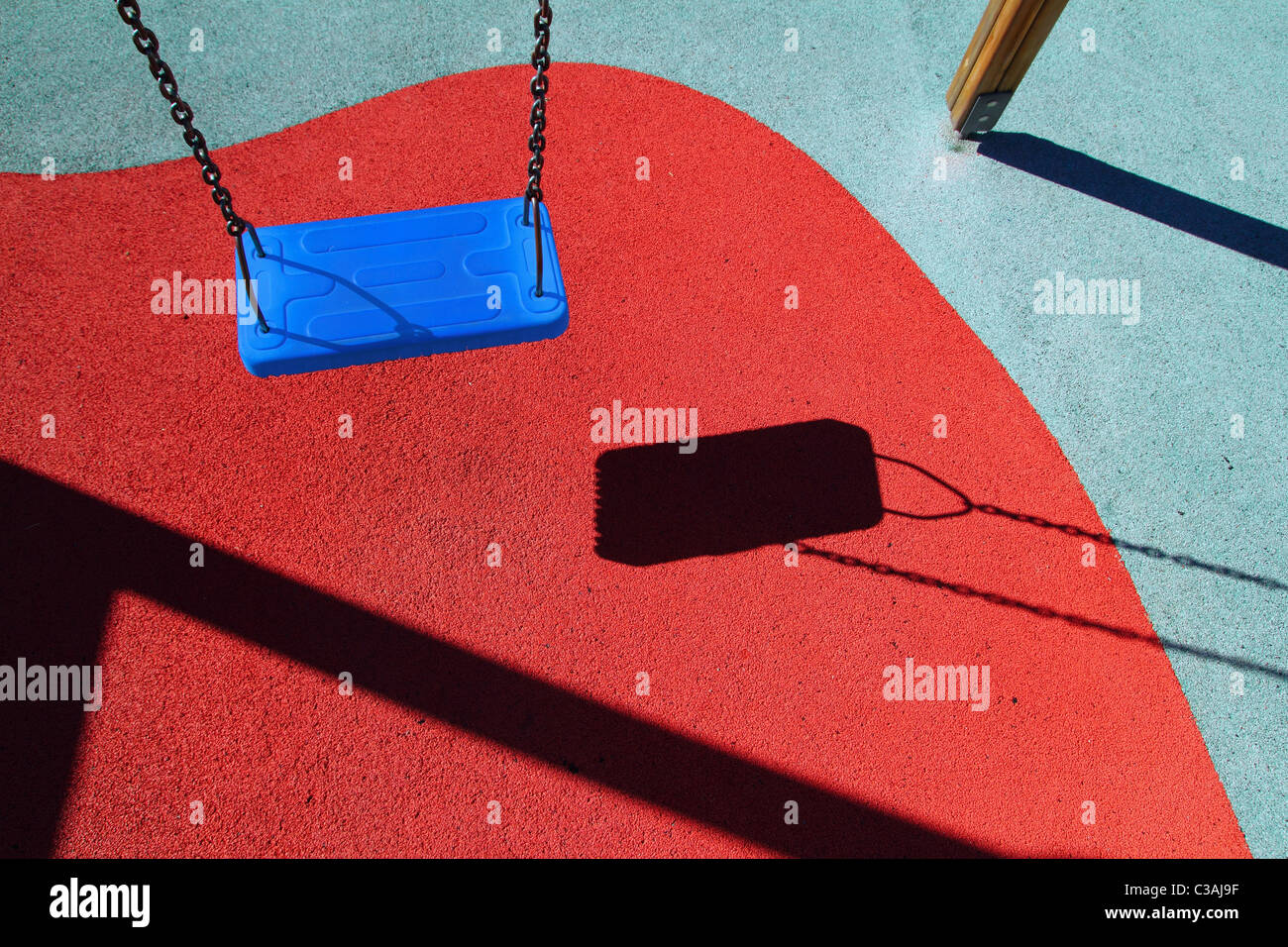 blue park swing or red floor children playground with shadows - Stock Image
