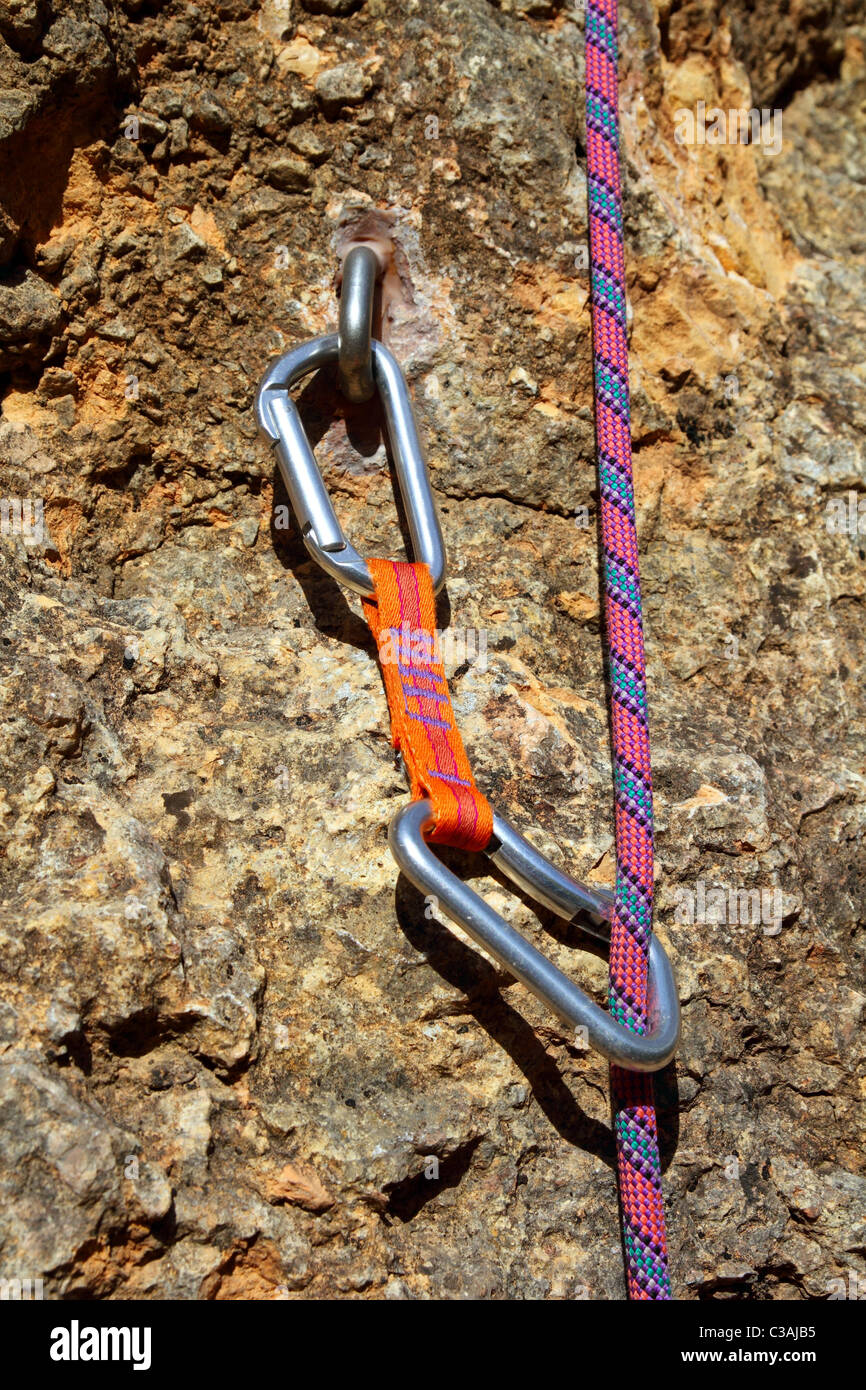 climbing shackles and rope on a rock wall vertical escalation - Stock Image