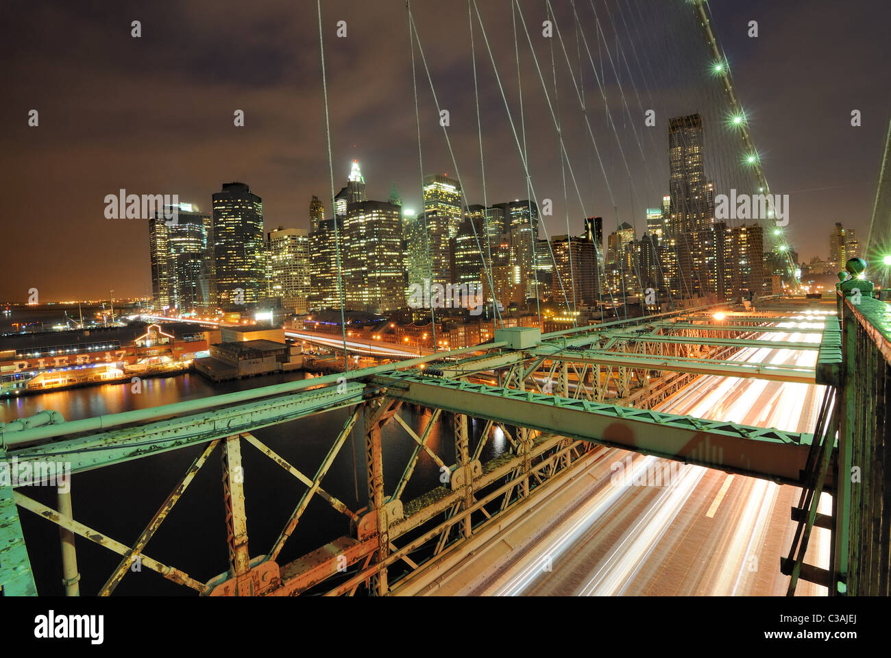 View of downtown Manhattan from the Brooklyn Bridge with traffic flying by. - Stock Image