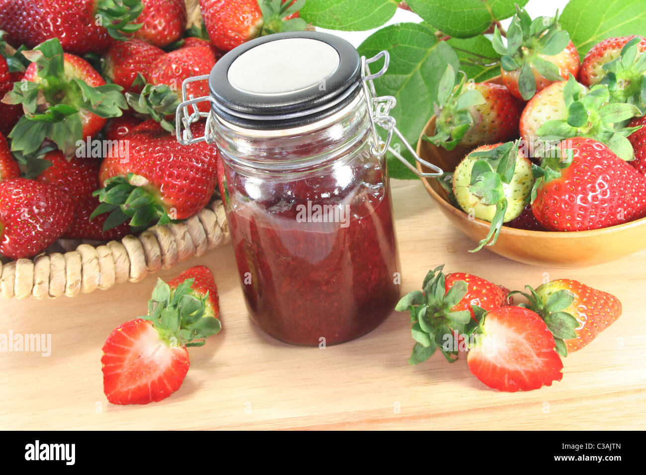 Strawberry jam with fresh strawberries on a wooden board - Stock Image