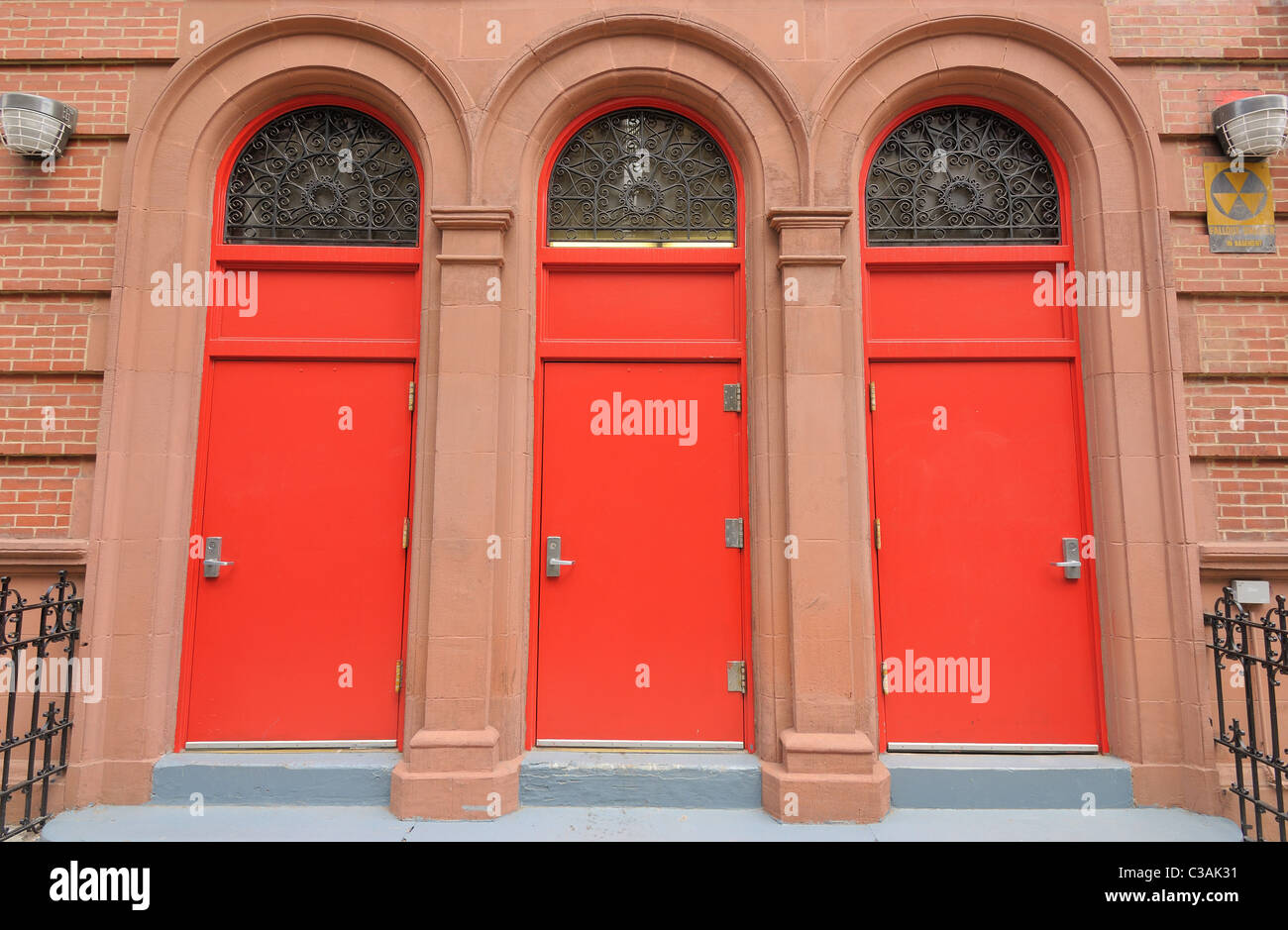 Three red doors at the entrance of a building. - Stock Image