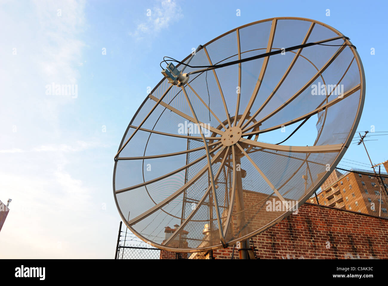 View from a rooftop in New York City with an old worn satellite dish receiver - Stock Image