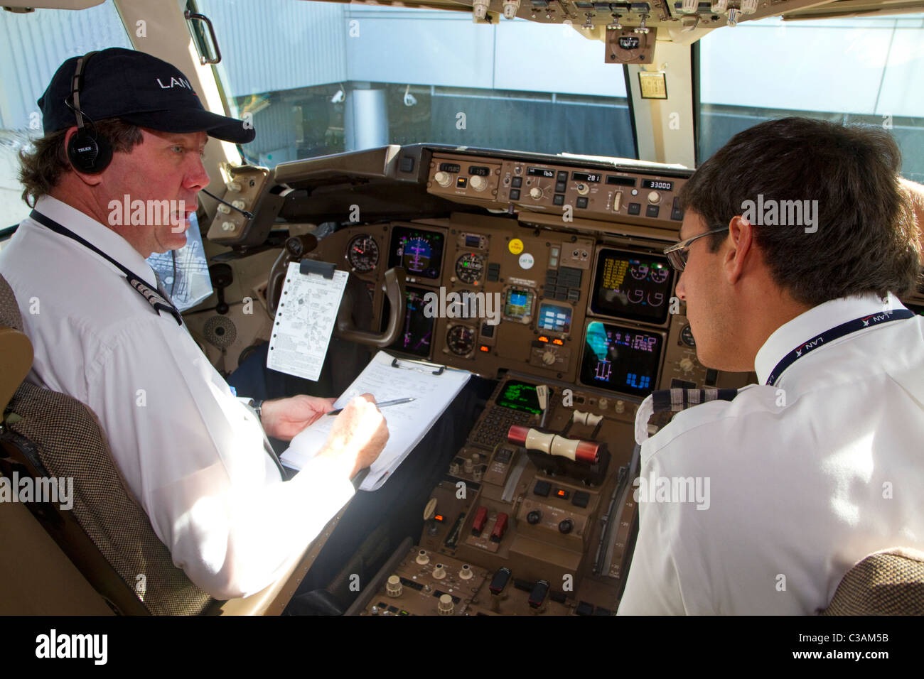 Pilot and first officer reviewing a pre-flight checklist in the cockpit of a Boeing 767 aircraft. - Stock Image