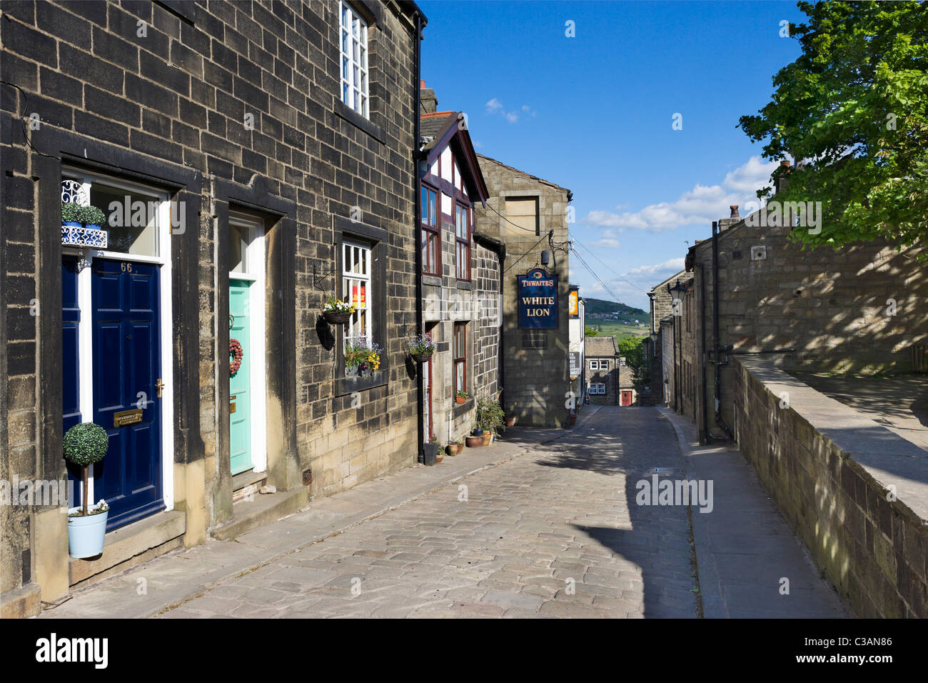 Traditional stone houses and village pub on the main street through Heptonstall, near Hebden Bridge, West Yorkshire, - Stock Image