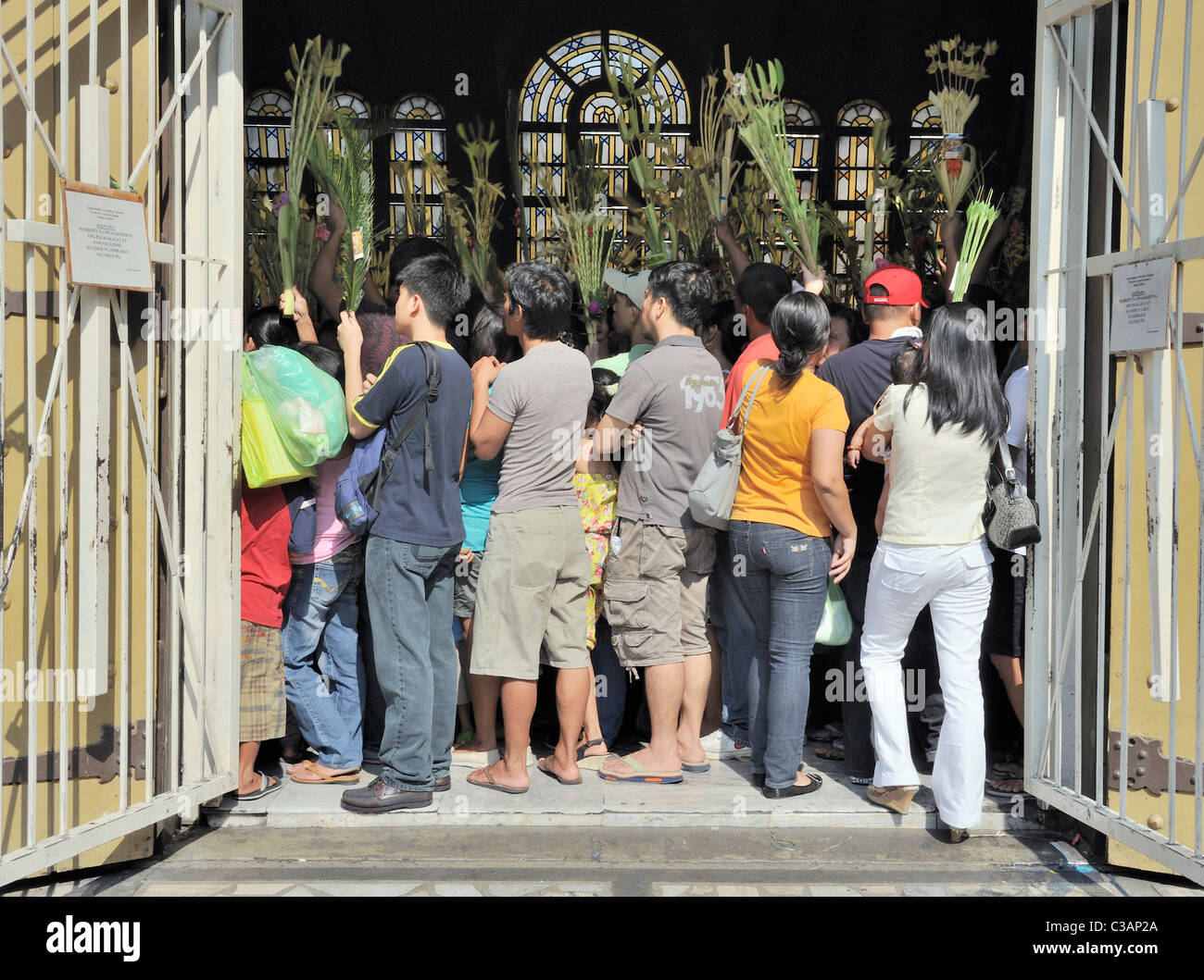 Filipinos crowd a church for the service on Palm Sunday - Stock Image