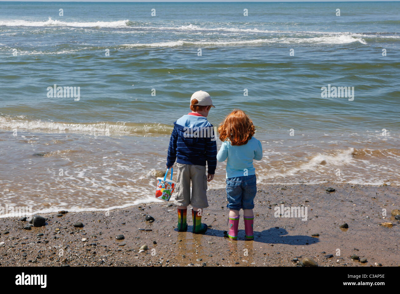 Two children, brother and sister on a beach with bucket and spade. - Stock Image