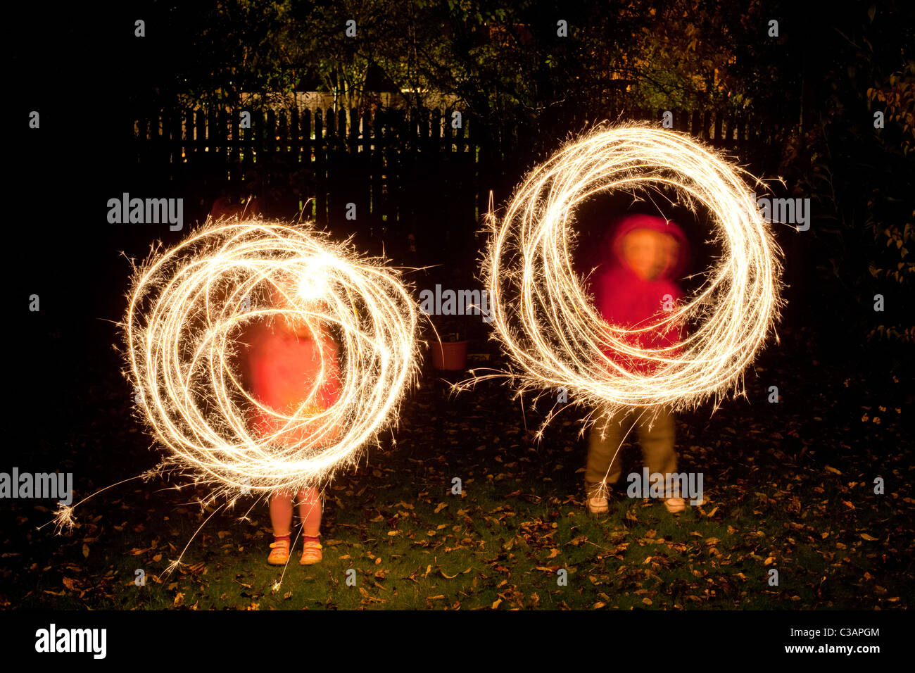 Children with sparklers in a garden - Stock Image