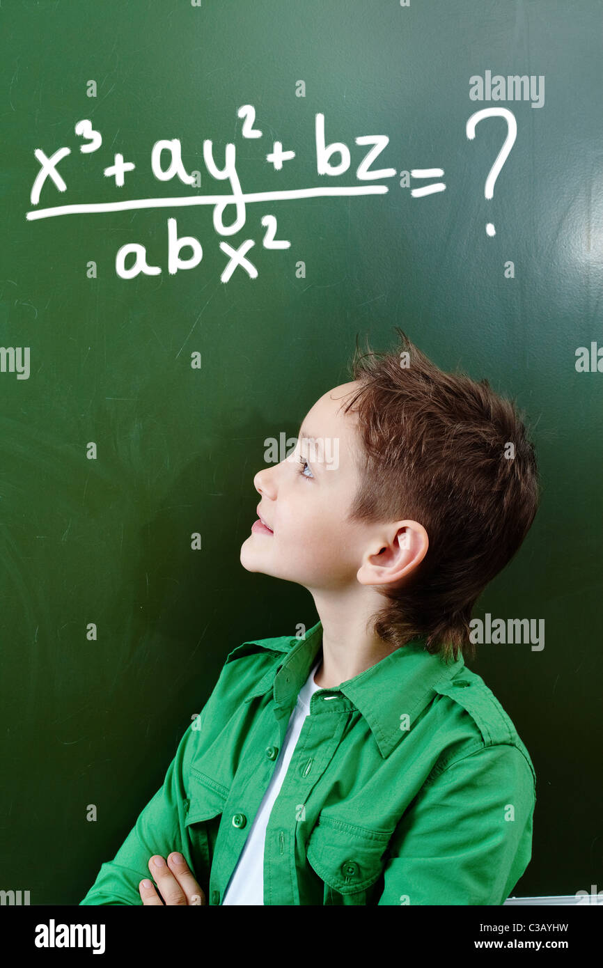 Portrait of smart lad looking at blackboard with algebraic formula on it - Stock Image