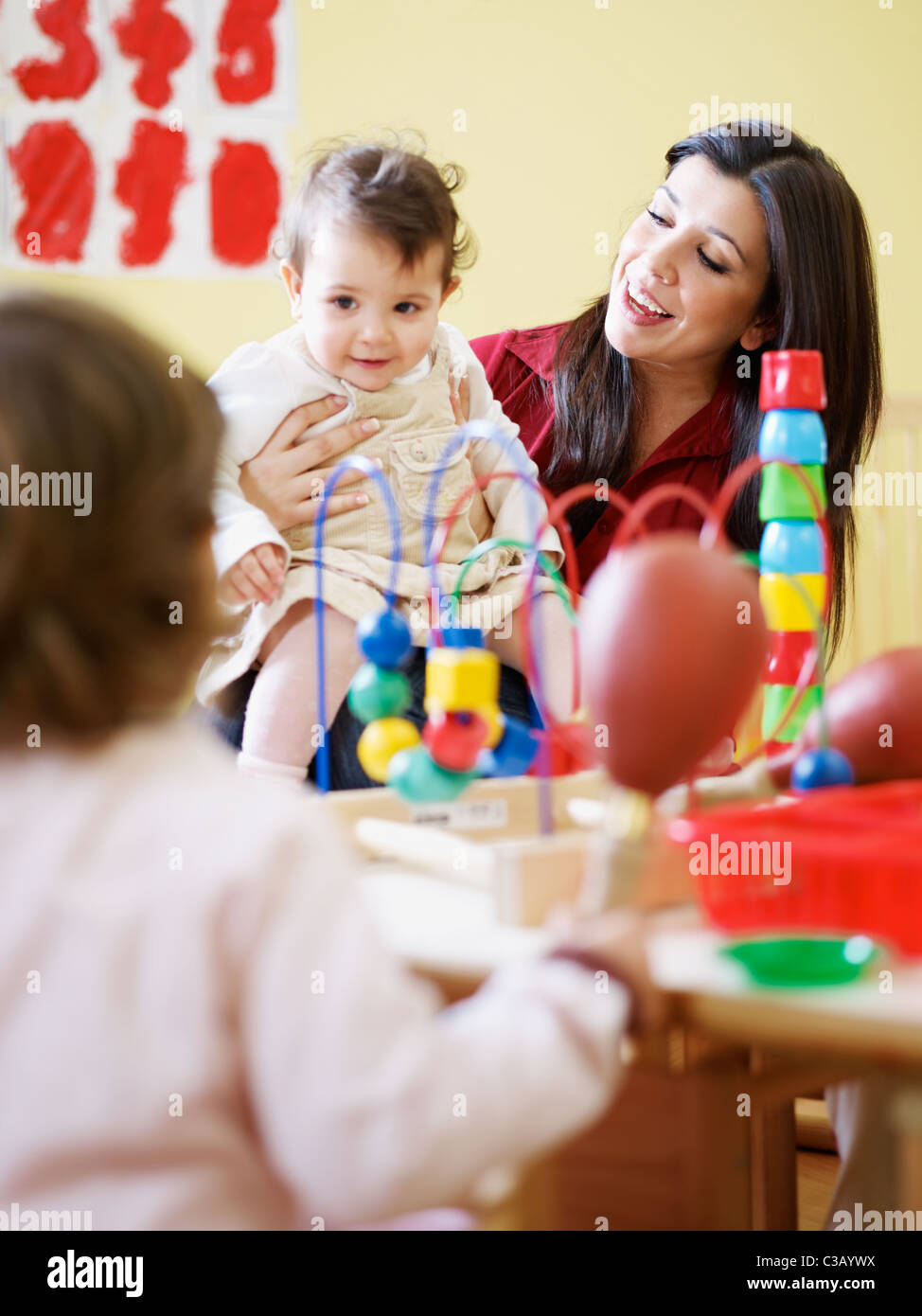 female toddler and 2-3 years girl playing with maraca in kindergarten. Vertical shape - Stock Image