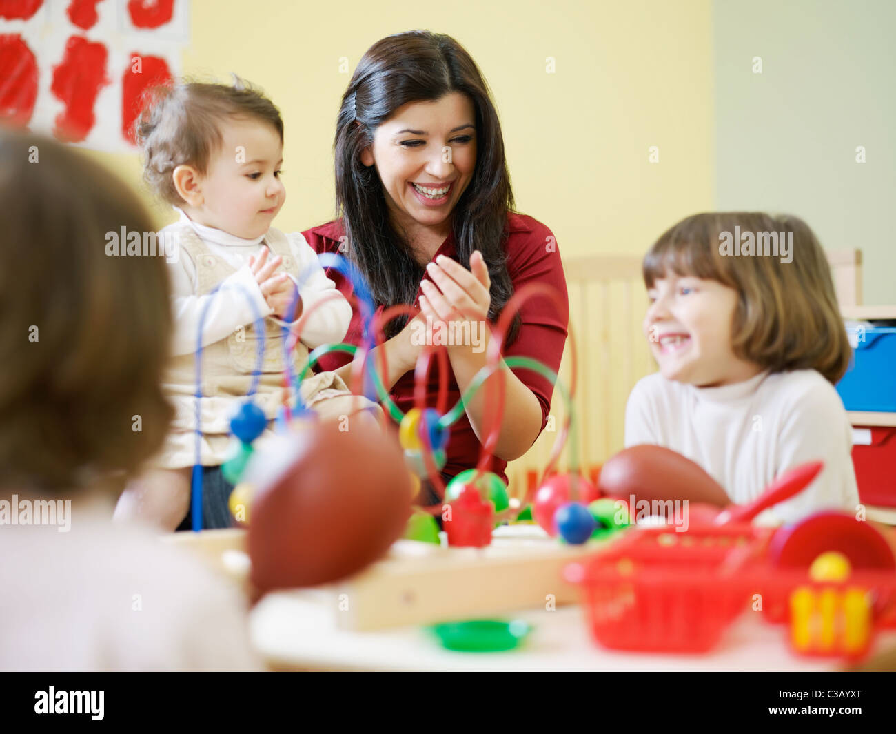 female toddler and 2-3 years girls playing with toys in kindergarten. Horizontal shape - Stock Image
