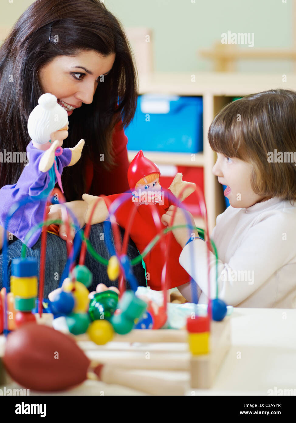 2-3 years girl playing with marionette in kindergarten. Vertical shape - Stock Image