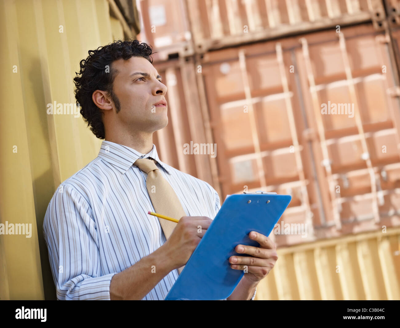 portrait of mid adult businessman leaning on cargo container and looking up. Horizontal shape, side view, copy space - Stock Image