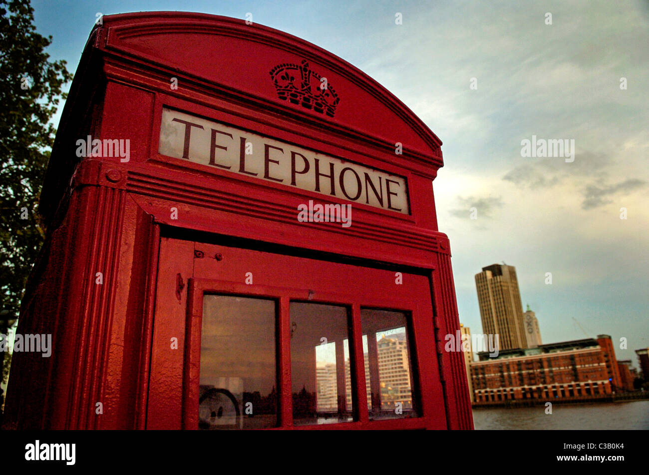 A classic telephone box by the Thames river - Stock Image
