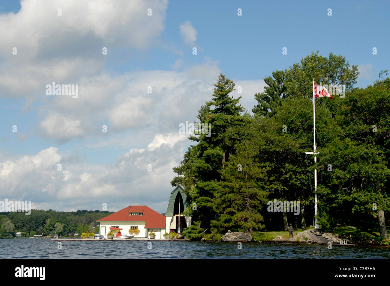 A holiday home on Lake Muskoka in Ontario's Cottage country in Canada. Note the church-shaped boat house. - Stock Image