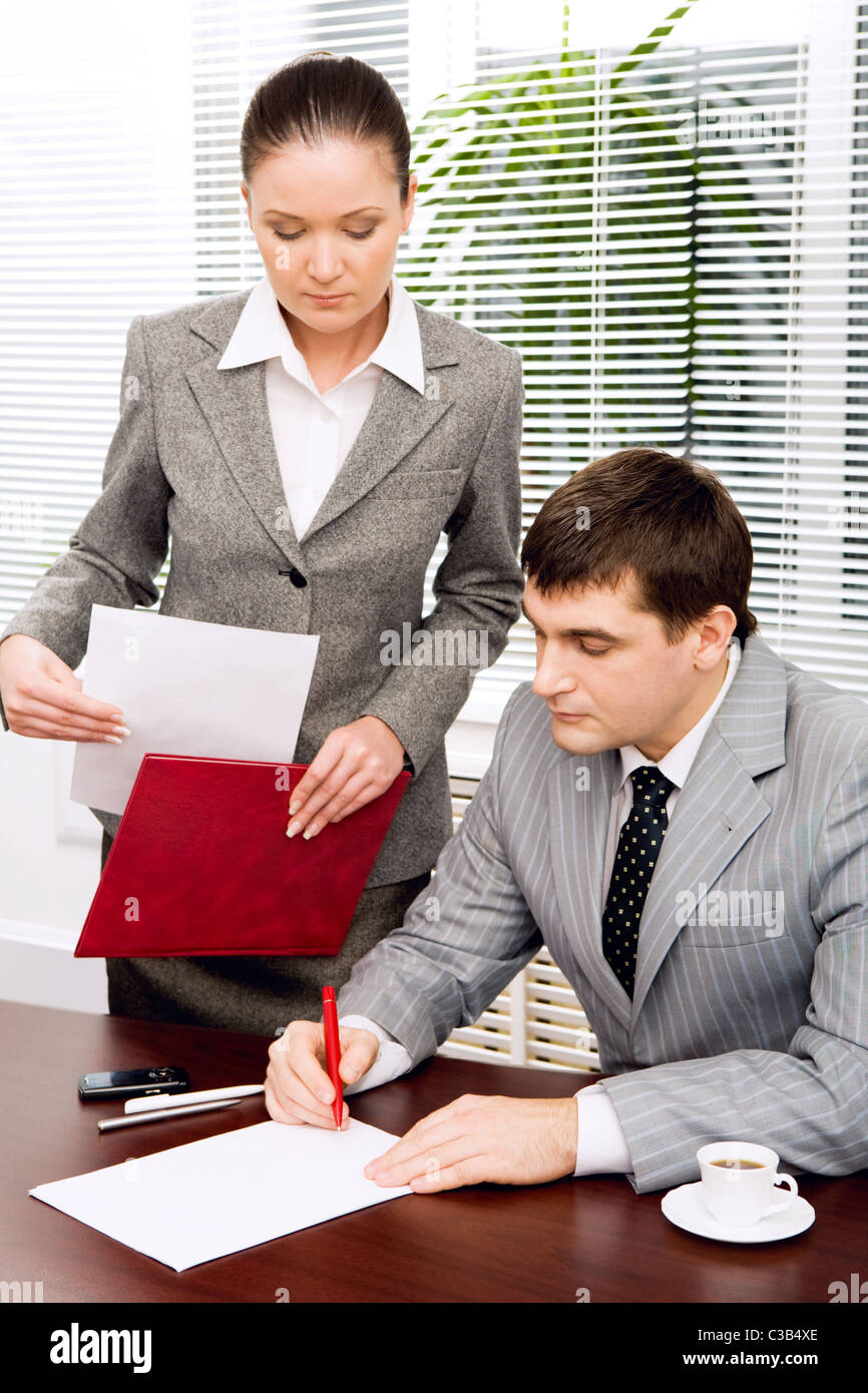 Portrait of serious boss signing contract with executive secretary near by - Stock Image
