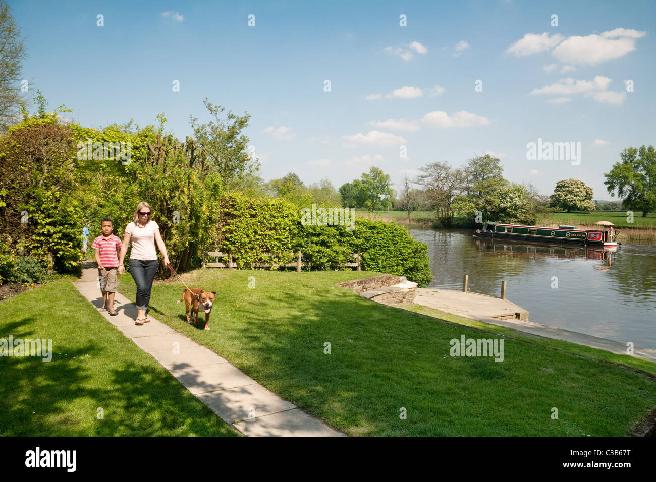 A family walking the dog on the river Thames path at Wallingford, Oxfordshire - Stock Image