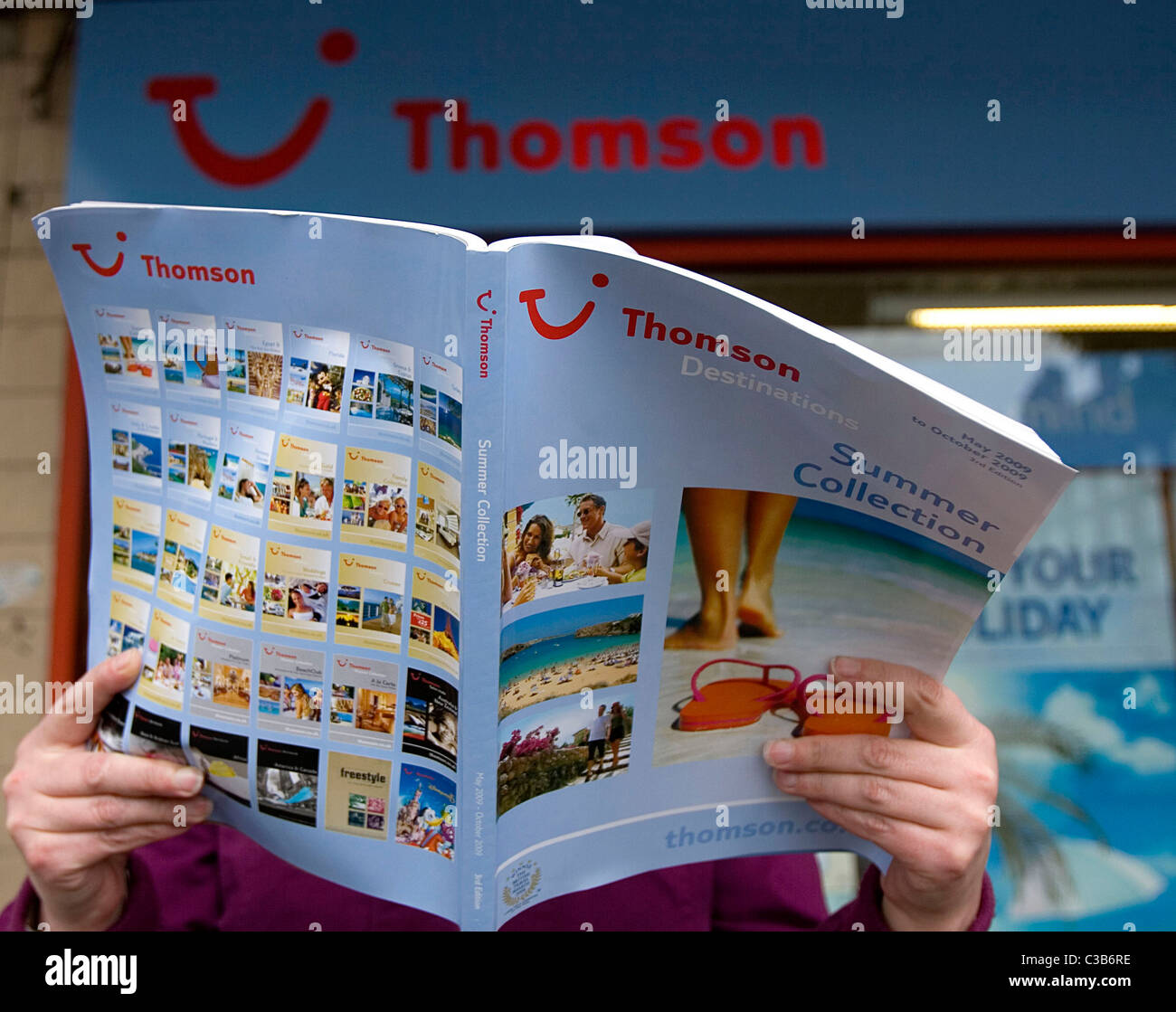 A woman browses a travel brochure outside a branch of Thomson travel agency. - Stock Image